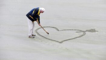 A man draws a heart in the sand